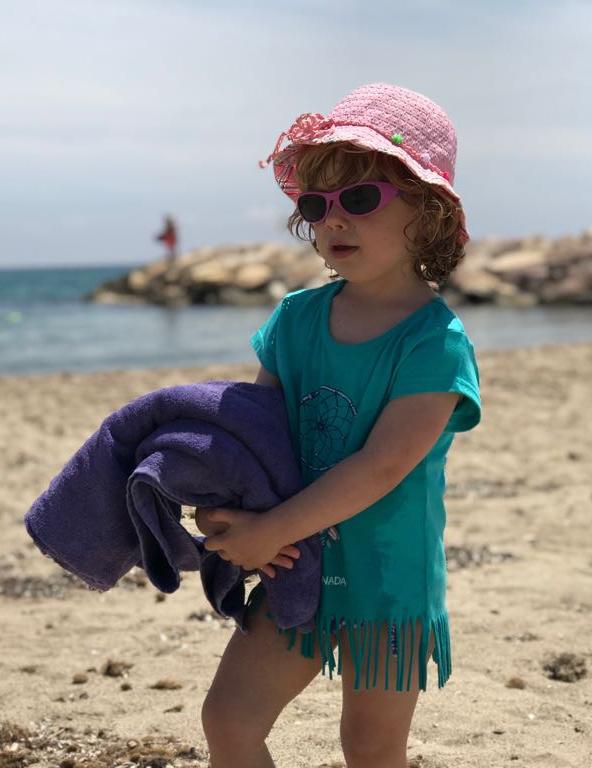 niña en la playa con gafas de sol